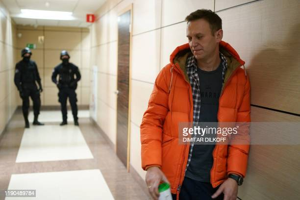 Russian opposition leader Alexei Navalny stands near law enforcement agents in a hallway of a business centre which houses the office of his...