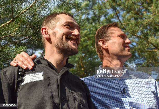 Russian opposition leader Alexei Navalny stands next to his younger brother Oleg as they smile in the village of Naryshkino in the Oryol region south...