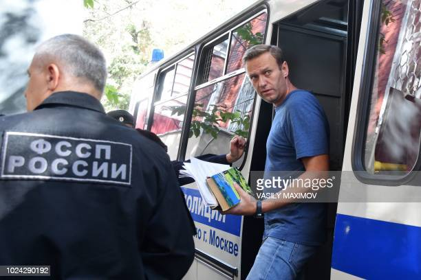 TOPSHOT Russian opposition leader Alexei Navalny steps out of a police bus as he arrives to the court for his trial in Moscow on August 27 2018...