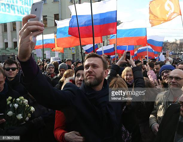 Russian opposition leader Alexei Navalny takes a selfie photo as his spouse Yulia Navalnaya looks on during a mass march marking the oneyear...