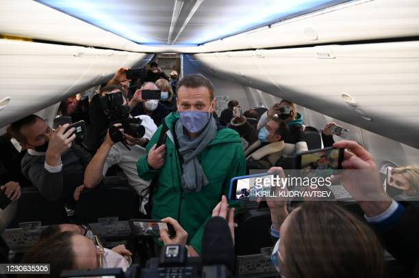 Russian opposition leader Alexei Navalny walks to take his seat in a Pobeda airlines plane heading to Moscow before take-off from Berlin Brandenburg...