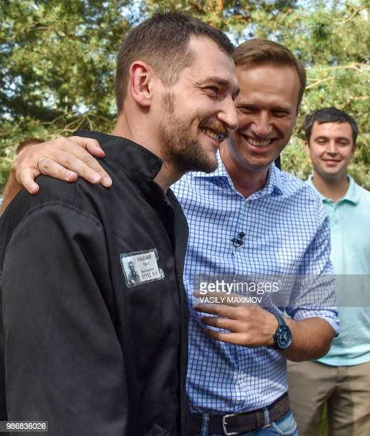 Russian opposition leader Alexei Navalny walks with his younger brother Oleg in the village of Naryshkino in the Oryol region south of Moscow on June...