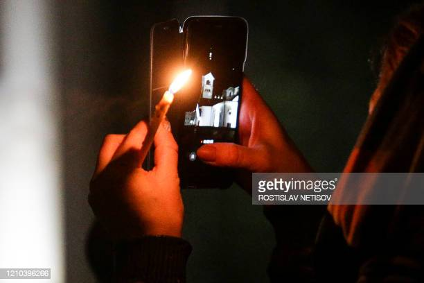 A Russian Orthodox believer holds a candle and a mobile phone as she attend the Orthodox Easter service outside the church in Novosibirsk early...