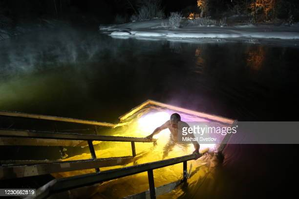 Russian Orthodox believer takes a dip in the icy cold water of the Istra river on January 18, 2021 in Istra, Russia. Orthodox Christians across...