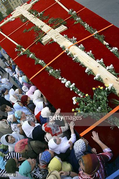 Russian Orthodox believers bow and touch a wooden cross at Novospassky Monastery in Moscow 06 August 2007 The cross which earlier in the day was...
