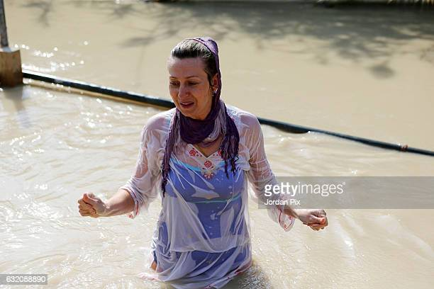 Russian Orthodox Christian pilgrim is being baptized in the muddy holy water of the River Jordan during the Epiphany celebrations at the baptismal...