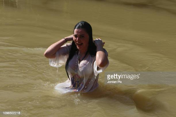 Russian Orthodox Christian pilgrims are being baptized in the due to the rain muddy holy water of the River Jordan during the Epiphany celebrations...