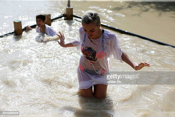 Russian Orthodox Christian pilgrims are being baptized in the muddy holy water of the River Jordan during the Epiphany celebrations at the baptismal...