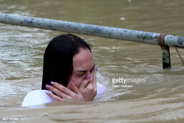 Russian Orthodox Christian pilgrims get baptized in the waters of the eastern bank of the Jordan River on January 19 2018 in Tal elKharrar Jordan...
