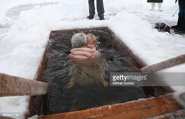 A Russian Orthodox man holds a young girl as they bathe in a small icy cold water pond as the air temperature drops to 10 C on January 19 2016 in...