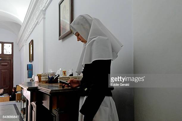 A Russian orthodox nun using a cellular phone in a church in the Chrustian quarter in Old city Of Jerusalem Israel