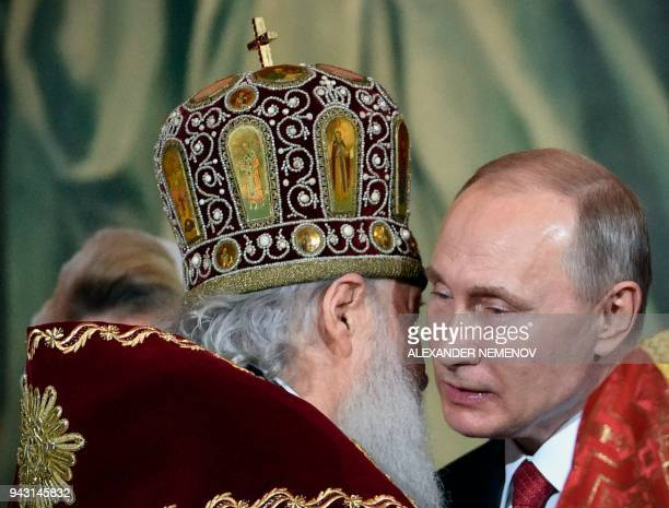Russian Orthodox Patriarch Kirill congratulates Russian President Vladimir Putin during an Orthodox Easter ceremony in Moscow early on April 8 2018 /...