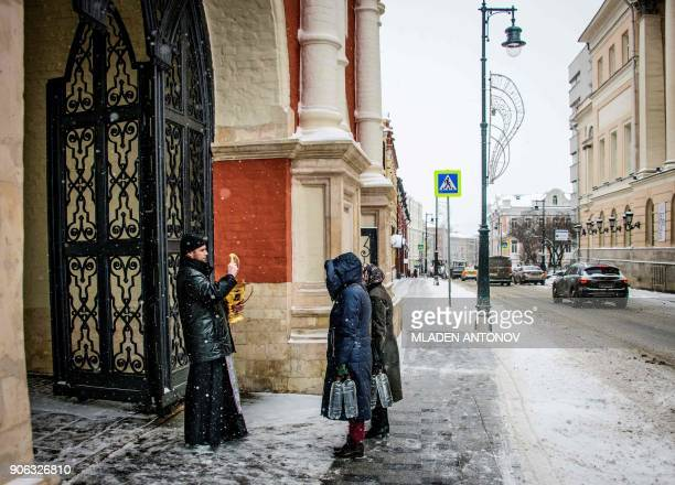 A Russian Orthodox priest blesses believers at the entrance to the Vysokopetrovsky Monastery in downtown Moscow on January 18 2018 Russia celebrates...