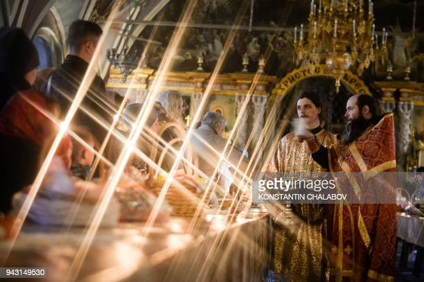 Russian Orthodox priest blesses cakes and colored eggs during an Orthodox Easter ceremony in The Holy TrinityStSergius Lavra in Sergiyev Posad on...