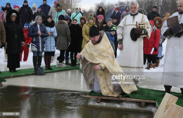 A Russian Orthodox Priest blesses icycold water of Peschanaya river as the air temerature droped to 8C on Epiphany on January 19 2018 in a villiage...