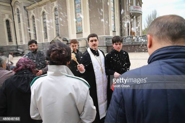 Russian Orthodox priest blesses worshippers and food for their Easter meal which they brought with them outside the Holy Transfiguration Cathedral on...