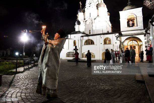 A Russian Orthodox priest conducts the Orthodox Easter service in a 17th century church on the outskirts of Moscow early on April 19 during a strict...