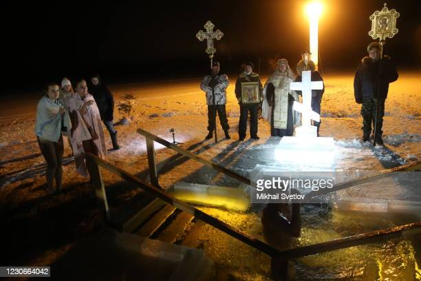 Russian Orthodox priest Nikolay Yelchev looks on as a believer takes a dip in the icy cold water of the Istra river on January 19, 2021 in Lamishino,...