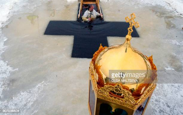 Russian Orthodox priest plunges into the icy waters of a lake during the celebration of the Epiphany holiday in the village of Orlino some 80 km of...