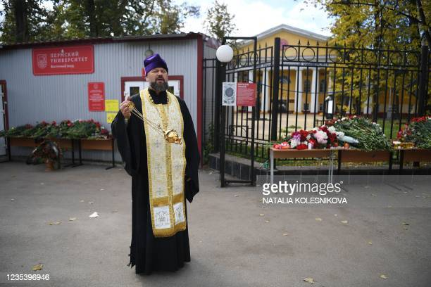 Russian Orthodox priest services at the entrance of the university campus in Perm on September 21, 2021 one day after a gunman killed six people on...