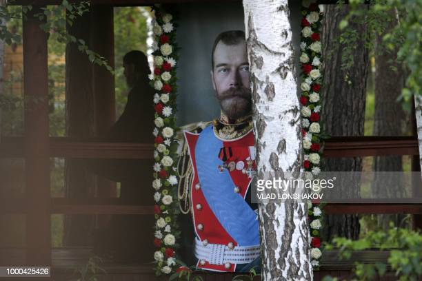 Russian Orthodox priest walks close to a portrait of the last Russian tsar Nicholas II during as he takes part in a nightime procession marking 100...