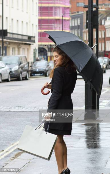 Russian outdoor girl fashion umbrella shopping in rainy Belgravia