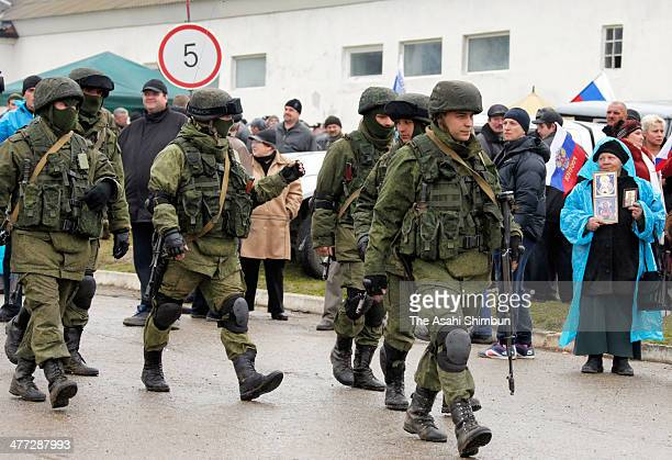 Russian paramilitaries are cheered by proRussian residents outside of a Ukrainian military base on March 7 2014 in Simferopol Ukraine Russian...