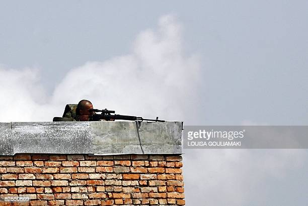 A Russian peacekeeper looks through his scope during a demonstration by Georgians outside the Russian base in Teklati near Poti in western Georgia on...