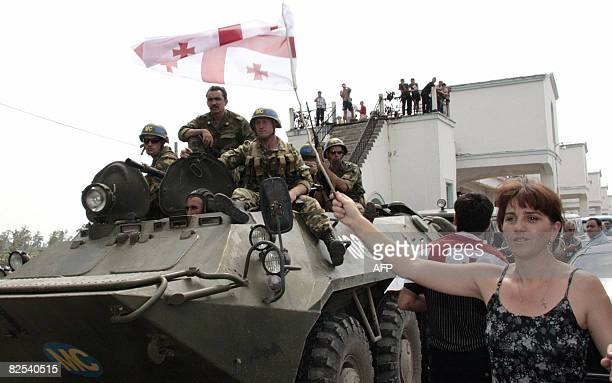 Russian peacekeeping soldiers sit on a top of APC as Georgian woman holds national flag in Poti on August 23 2008 NATO insisted Saturday that Russian...