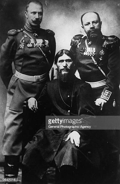 Russian peasant and mystic Grigory Yefimovich Rasputin centre former peasant and selfstyled holy man sitting between two military men in uniform...