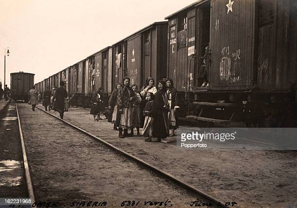 Russian peasant families waiting to board boxcars at the train station at Omsk Siberia on 1st June 1908