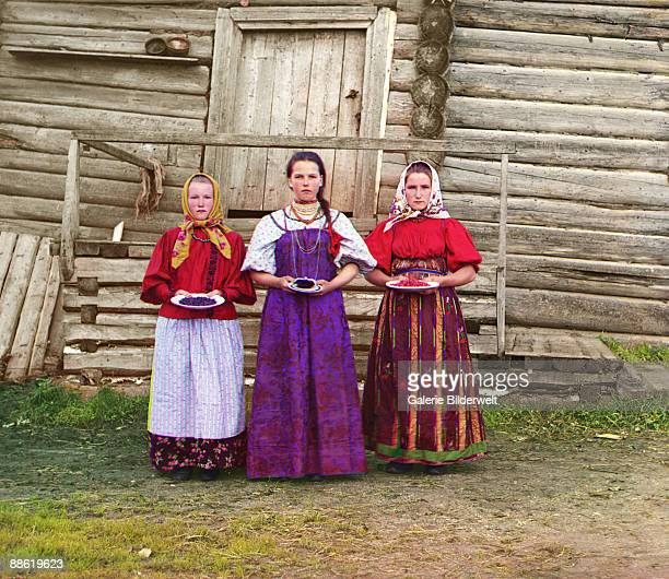 Russian peasant girls offer berries to visitors to their izba a traditional wooden house in a rural area along the Sheksna River near the small town...