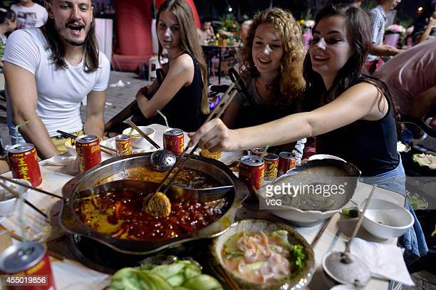 Russian people dip mooncakes into a hot pot on September 8 2014 in Chongqing Sichuan province of China Russian people eat mookcakes to celebrate...