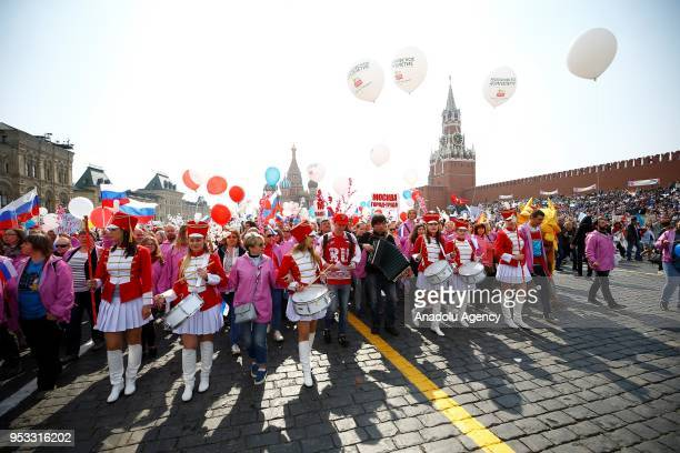 Russian people with flowers and flags take part in a rally to mark May Day International Workers' Day at the Red Square in Moscow Russia on May 1 2018