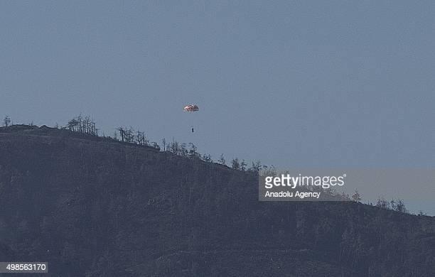 Russian pilot parachutes out of a warplane which went down in Syria's northwestern Turkmen town of Bayirbucak near Turkeys border on November 24,...