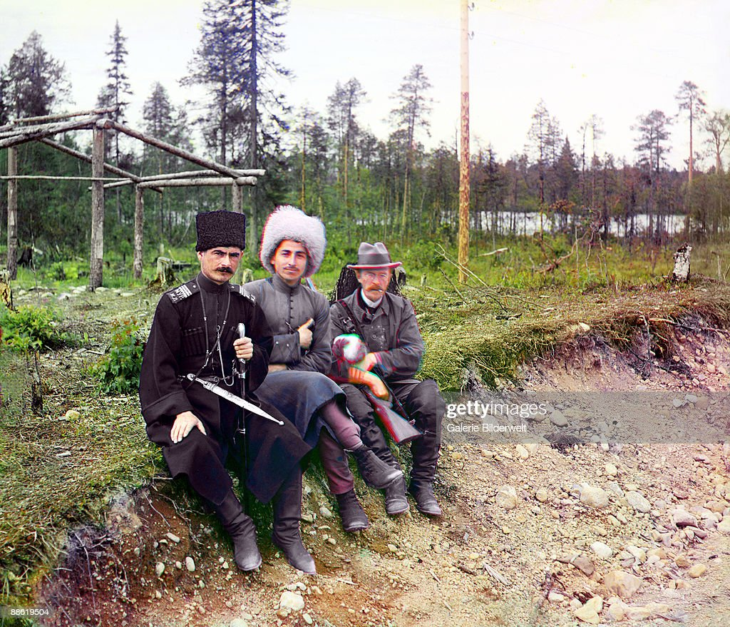 Russian pioneer of colour photography Sergey Prokudin-Gorsky (1863 - 1944, right) with two men in Cossack dress on the Murmansk Railway, Russian Empire, 1915. Under the sponsorship of Tsar Nicholas II, Prokudin-Gorsky toured the Russian Empire by rail between 1905 and 1915, documenting its culture and landscape in a collection of colour photographs.