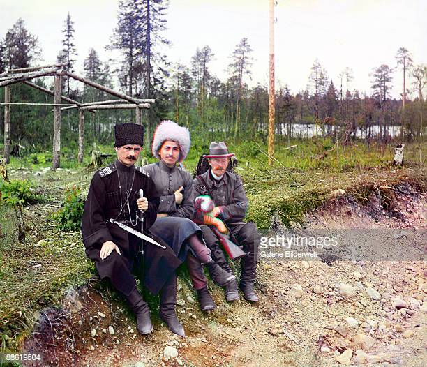 Russian pioneer of colour photography Sergey ProkudinGorsky with two men in Cossack dress on the Murmansk Railway Russian Empire 1915 Under the...