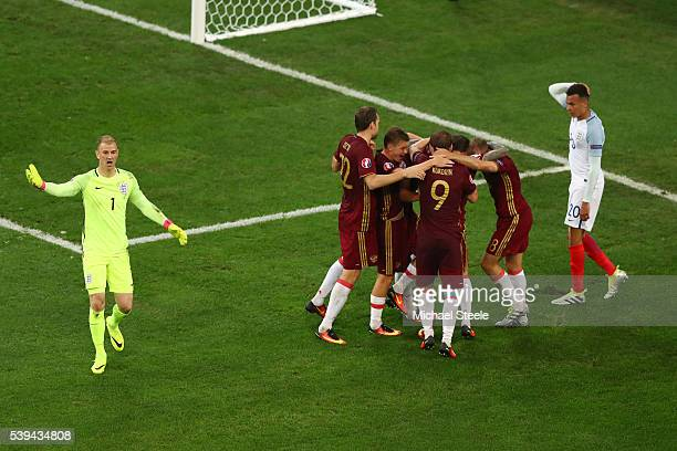 Russian players celebrate their team's first goal while Joe Hart and Dele Alli of England show their frustration during the UEFA EURO 2016 Group B...