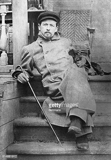 Russian poet Anton Chekov reclines on the steps of a house