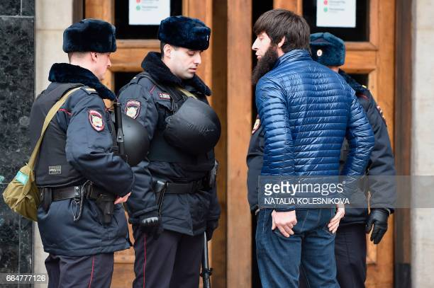 Russian police officers check ID papers of a passenger at the entrance to Ploschad Revolyutsii metro station on April 5 2017 in Moscow as security...