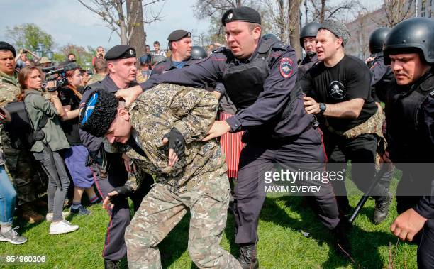 Russian police officers detain a cossack during an unauthorized antiPutin rally called by opposition leader Alexei Navalny on May 5 2018 in Moscow...