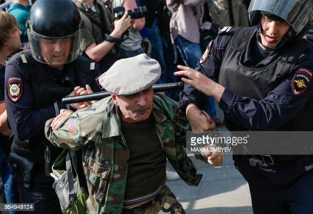 Russian police officers detain a participant of an unauthorized anti-Putin rally called by opposition leader Alexei Navalny on May 5, 2018 in Moscow,...