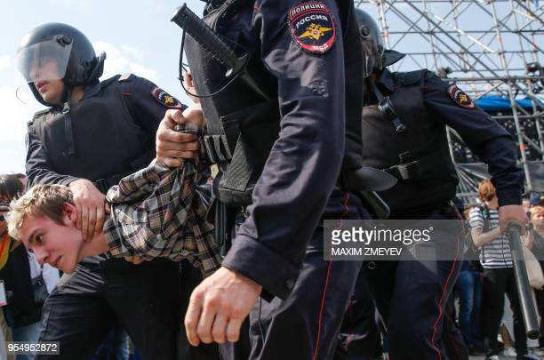 TOPSHOT Russian police officers detain a participant of an unauthorized antiPutin rally called by opposition leader Alexei Navalny on May 5 2018 in...