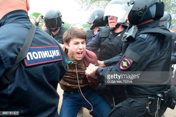 TOPSHOT Russian police officers detain a participant of an unauthorized opposition rally in Saint Petersburg on June 12 2017 Over 200 people were...