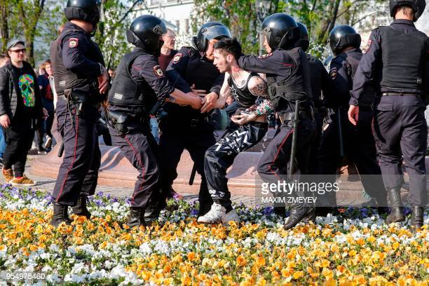 Russian police officers detain a protester during an unauthorized antiPutin rally called by opposition leader Alexei Navalny on May 5 2018 in Moscow...
