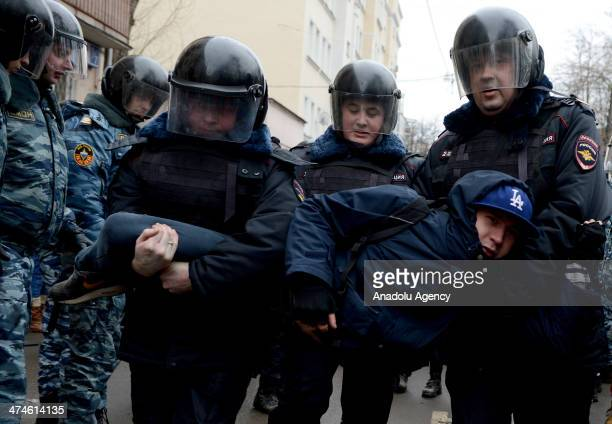 Russian police officers detain an opposition activist outside a court room during the ''Bolotnaya'' trial in Moscow, Russia on February 24, 2014. A...