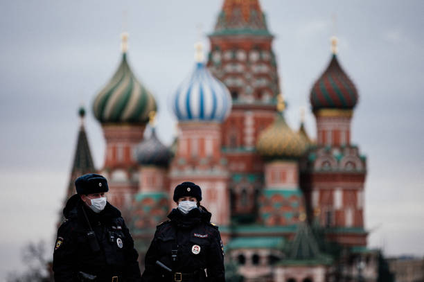 TOPSHOT Russian police officers patrol on March 30 2020 on the deserted Red square in front of Saint Basil's Cathedral in Moscow as the city and its...