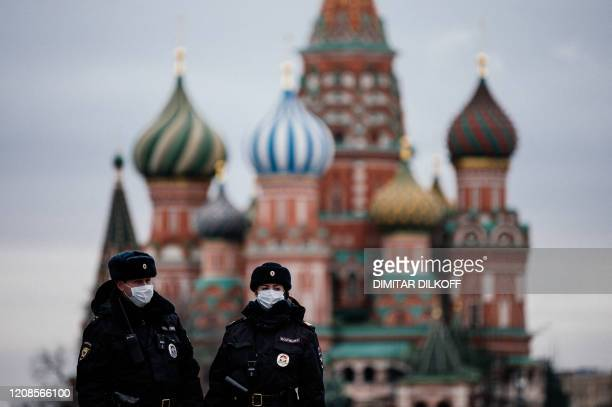 Russian police officers patrol on March 30, 2020 on the deserted Red square in front of Saint Basil's Cathedral in Moscow as the city and its...