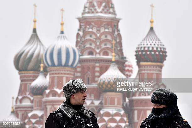 Russian police officers patrol Red Square under a snowfall with St Basil's Cathedral seen in the background in central Moscow on January 27 2016 AFP...
