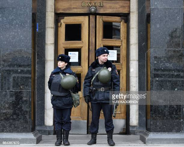 Russian police officers stand guard at the entrance to Ploschad Revolyutsii metro station on April 4 2017 in Moscow as security measures are...